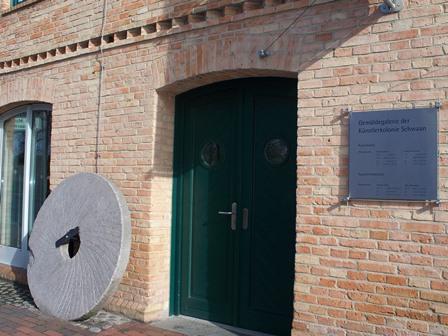 Das Bild zeigt die Eingangstür und das alte Mühlrad
